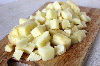 Помытый очищенный и порезанный кубиками картофель