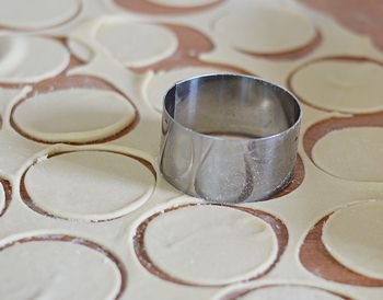 Из раскатанного тонким слоем тесто вырезаются кружки металлическим кольцом