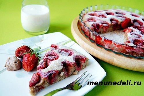 Готовый кусок пирога с клубникой на тарелке со стаканом молока