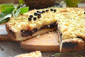 Разрезанный тертый песочный пирог со смородиновым вареньем