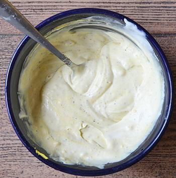 Перемешанные в тарелке яичные желтки со сметаной солью и черным перцем