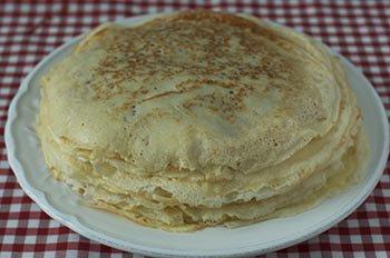 Стопка тонких готовых блинчиков на молоке на ужин или завтрак
