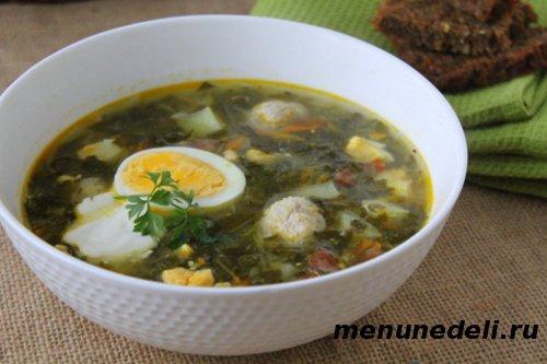 Суп  из консервированного щавля с яйцом кабачком и фрикадельками в тарелке