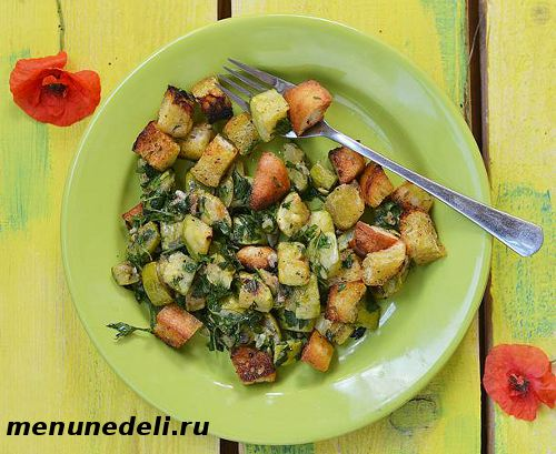 Теплый салат из кабачков с гренками и зеленью на тарелке