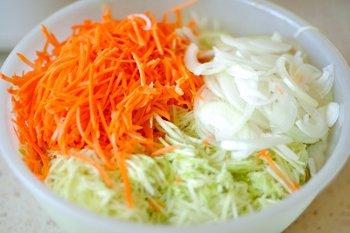 Тертые кабачки морковь и порезанный лук в большой миске