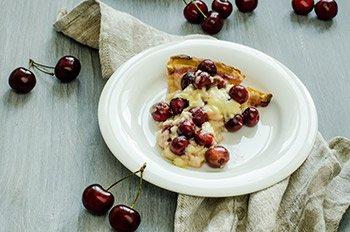 Кусочек готового вишневого пирога с заварным кремом на тарелке