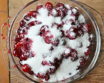 Вымытая вишня без косточек засыпана сахаром в миске