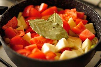 К луку и сельдерею добавляются помидоры картофель и бульон