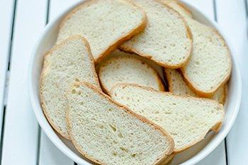 Хлеб нарезанный ломтиками выложен в форму для запекания