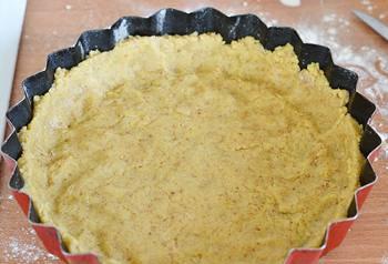 Раскатанное тесто выложено в форму для вишневого пирога