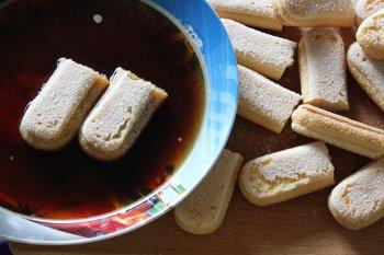 Бисквитное печенье разрезанное пополам обмакивается в горячий кофе