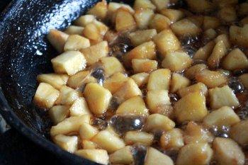 Порезанные кубиками яблоки жарятся на сливочном масле с сахаром