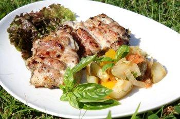Готовый шашлык из куриных бедрышек  с овощами на тарелке