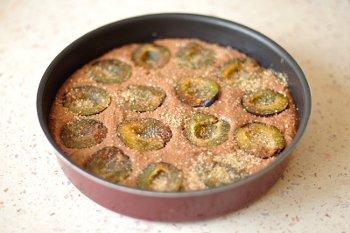 Тесто в подготовленной форме с утопленными в него половинками фруктов