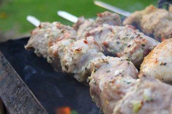 Вкусный шашлык из свиной шейки жарится на шампурах