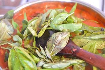 Добавляем в сотейник листья базилика помидоры соль и сахар