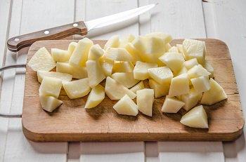 Очищенная картошка крупно порезанная кубиками для приготовления грибного супа