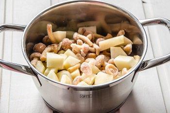 Кастрюля с порезанной картошкой и замороженными грибами