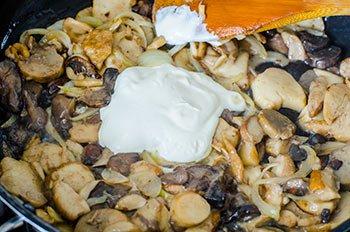 Добавляем сметану в грибы и тушим 10 минут.