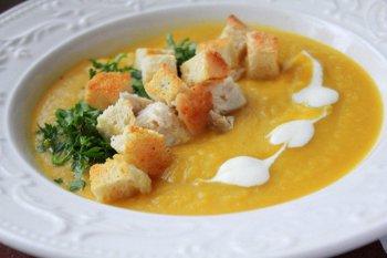 Суп пюре из тыквы поданный с сухариками зеленью и сметаной