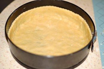 Раскатанное тесто выложено в форму со съемными бортиками