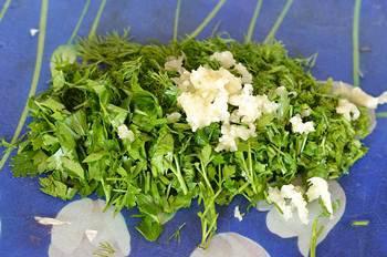 Порезанная зелень и измельченный чеснок для добавления в украинский борщ