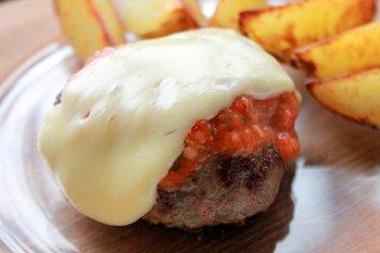Готовый бифштекс с томатным соусом и расплавленным сыром поданный с картофелем