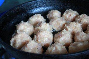 Круглые фрикадельки обжариваются на сковороде