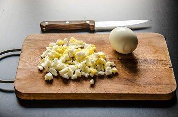 Очищенное и отваренное куриное яйцо порезанное мелким кубиком