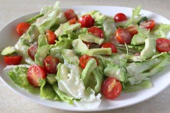 К листьям салата добавляется порезанные авокадо и помидоры