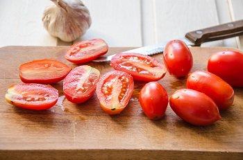 Мытые помидоры нарезанные на половинки для приготовления конфи