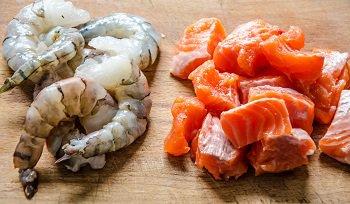 Очищенные креветки и порезанный лосось для добавления в суп