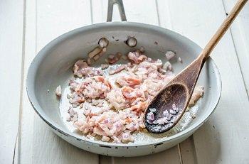 Лук и бекон обжариваются в сковороде до прозрачности