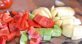 Порезанные крупными кубиками картофель кабачок помидоры и болгарский перец