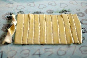 Слоеное тесто нарезается на полоски толщиной 1 сантиметр