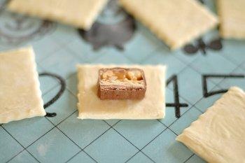 Кусочек сникерса выложенный на слоеное тесто