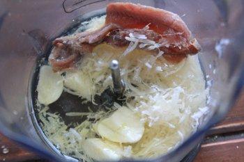 В блендере смешиваются сыр анчоусы чеснок