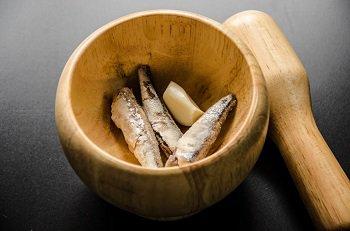 Анчоусы и чеснок растираются в деревянной ступке