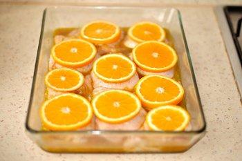 Курица в апельсиновом маринаде накрытая кусочками апельсина