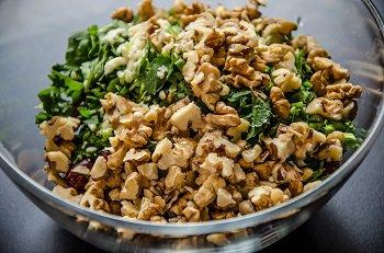 Крупно порезанные орехи и зелень добавляются к промытой фасоли
