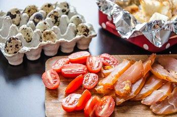 Порезанные помидоры копченная курица и перепелиные яйца