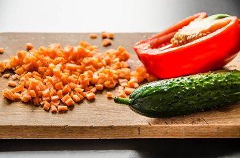 Очищенная и порезанная кубиком морковь огурец и болгарский перец