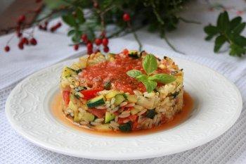Рис с помидорами и цуккини сформированные в кольце и политые томатным соусом