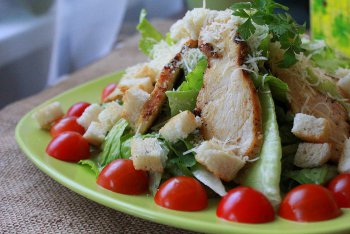 Салат цезарь с курицей сухариками и помидорами приготовленный дома