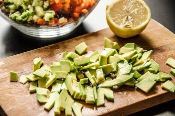 Порезанный авокадо сбрызгивается лимонным соком