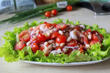 На салатные листья выложена смесь из креветок помидоров фасоли и лука
