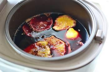 Глинтвейн с фруктами и специями варится в микроволновке