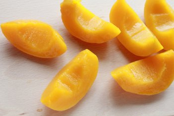Половинки персиков порезанные на четвертинки с вырезанными углублениями