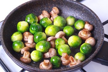 Брюссельская капуста и грибы обжариваются на сковороде