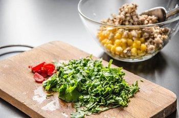 Порезанная кинза со жгучим перцем в салат из кукурузы